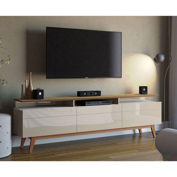 Sala planejada simples com um raque branco e tv presa na parede.