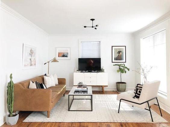 Sala simples branca com sofá de couro.
