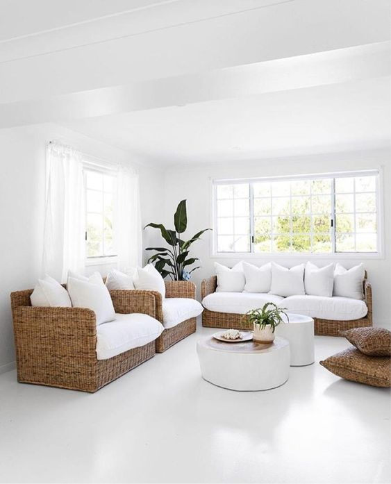 Sala branca com muitas almofadas na mesa cor e vasos de plantas.