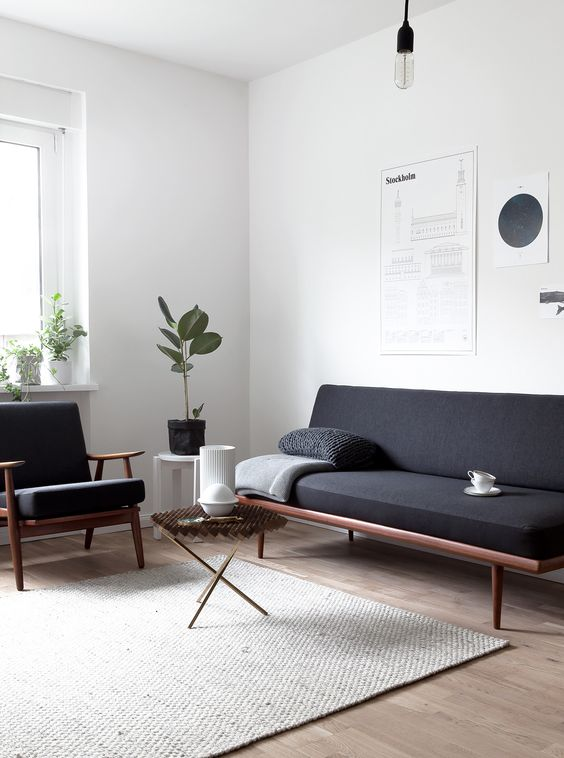 Sala minimalista com móveis pretos.