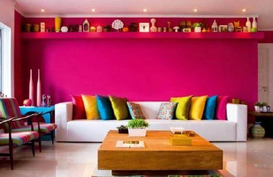 Parede rosa, sofá branco e almofadas coloridas.
