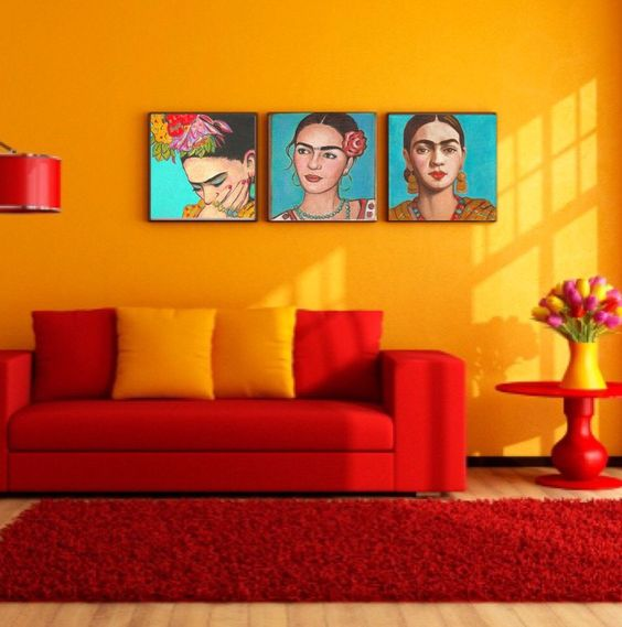 Parede amarela, sofá e tapete vermelhos e quadros coloridos.