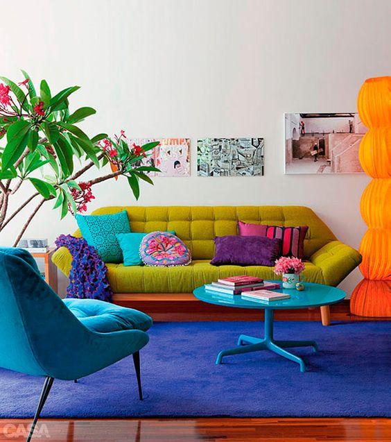 Sala com parede branca, sofá mostarda e poltrona azul.