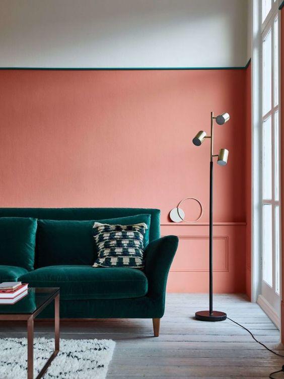 Sala planejada com parede rosa e sofá verde escuro.