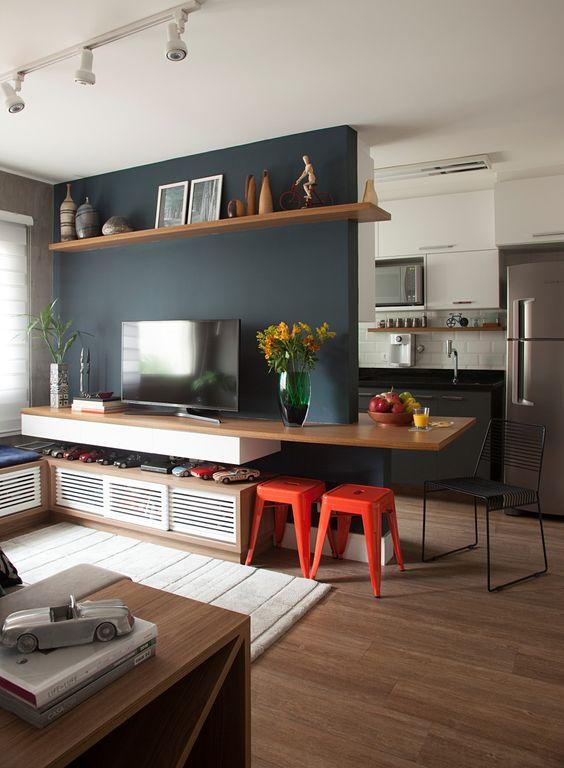 Sala planejada com móvel único de madeira que serve de apoio para a tv e como mesa.