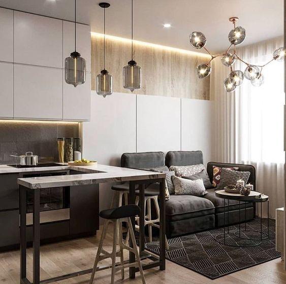 Sala e cozinha integrados com lustres modernos.
