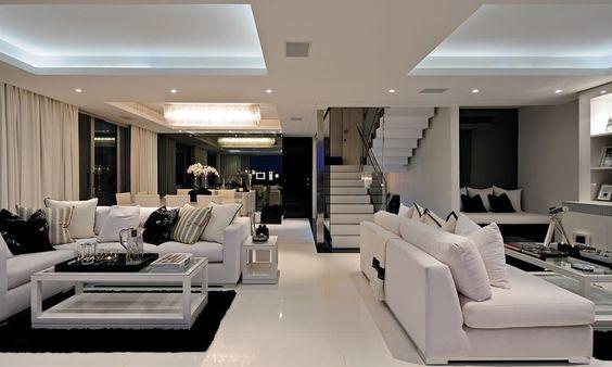 Salas de estar, de tv e de jantar com móveis brancos e detalhes pretos.