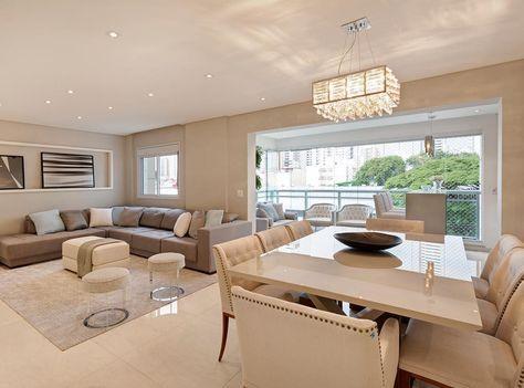 """Sala de estar com sofá em """"L"""" integrada com sala de jantar com mesa de oito cadeiras."""