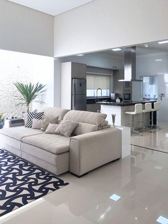 Sala planejada integrada com a cozinha e dividida por um sofá claro.