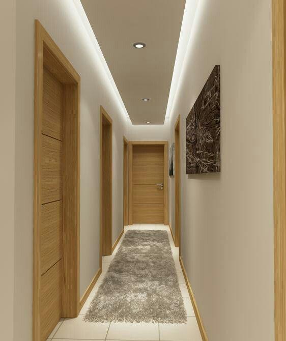Corredor com portas de madeira, tapete e quadros nas paredes.