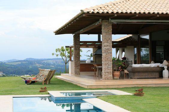 Varanda com móveis ao lado da piscina.