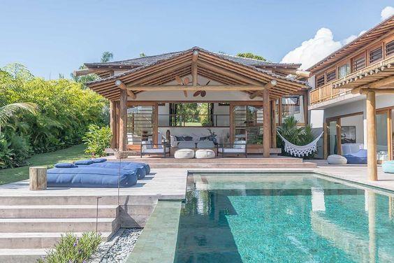 Casa de campo com piscina, rede e camas.