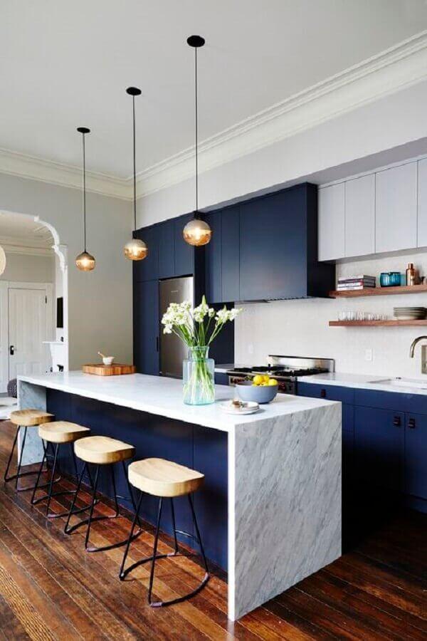 Cozinha pequena com móveis em azul marinho.