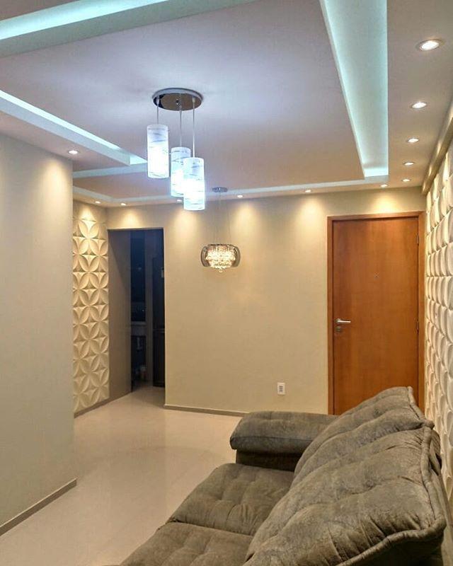 Sala com duas paredes de textura e sofá escuro.