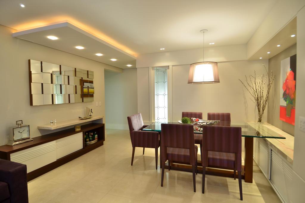Sala de jantar com espelhos e artigos decorativos.