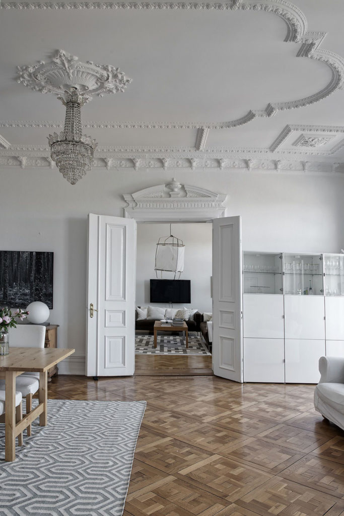 Grande cômodo branco com desenhos feitos de gesso no teto.