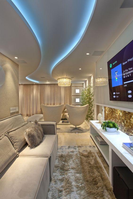 Sala com parede de textura, sofá cinza claro e almofadas decorativas.
