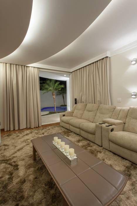 Sala com dois sofás cor creme, tapete, mesa de centro e cortinas nude.