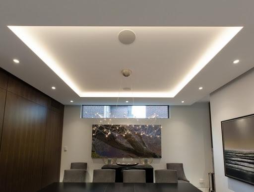 Sala decorada com lustre futurista e quadros.
