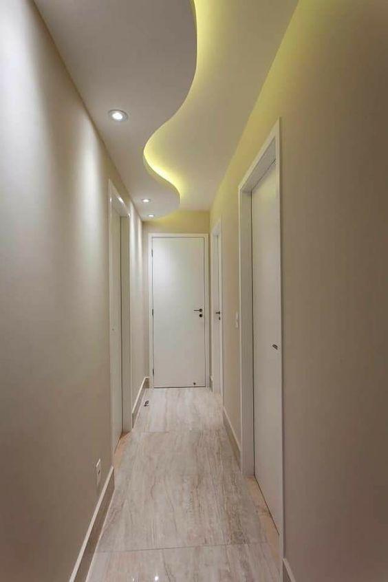 Corredor com paredes de cores neutras e portas brancas.