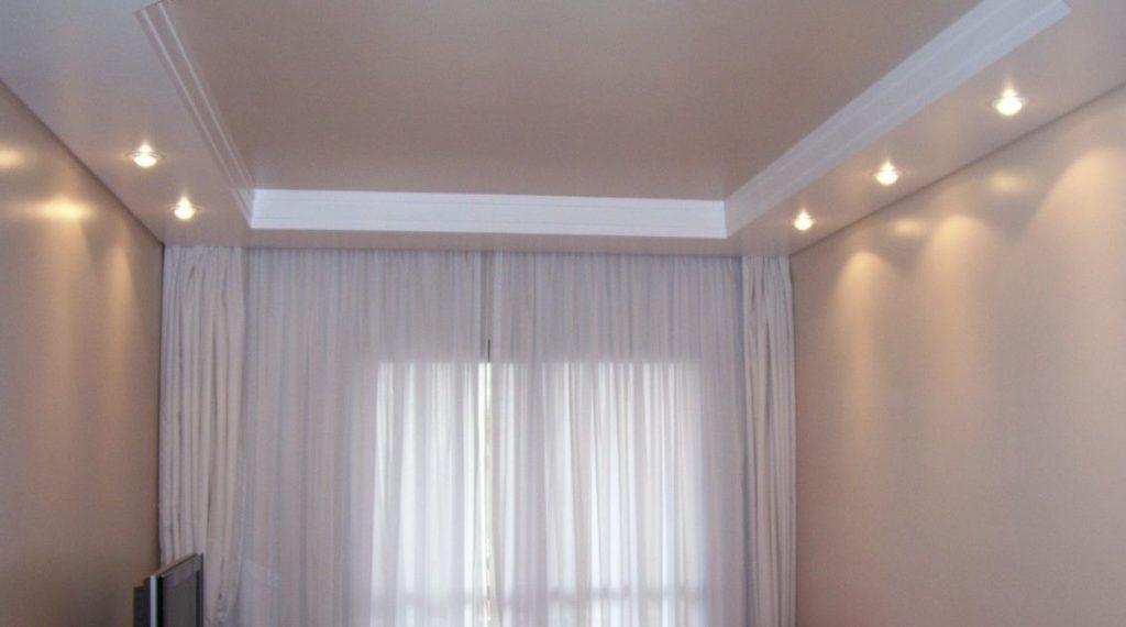 Sala de tv com cortinas brancas e iluminação embutida.