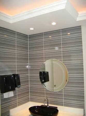 Banheiro com sanca fechada e pia preta.
