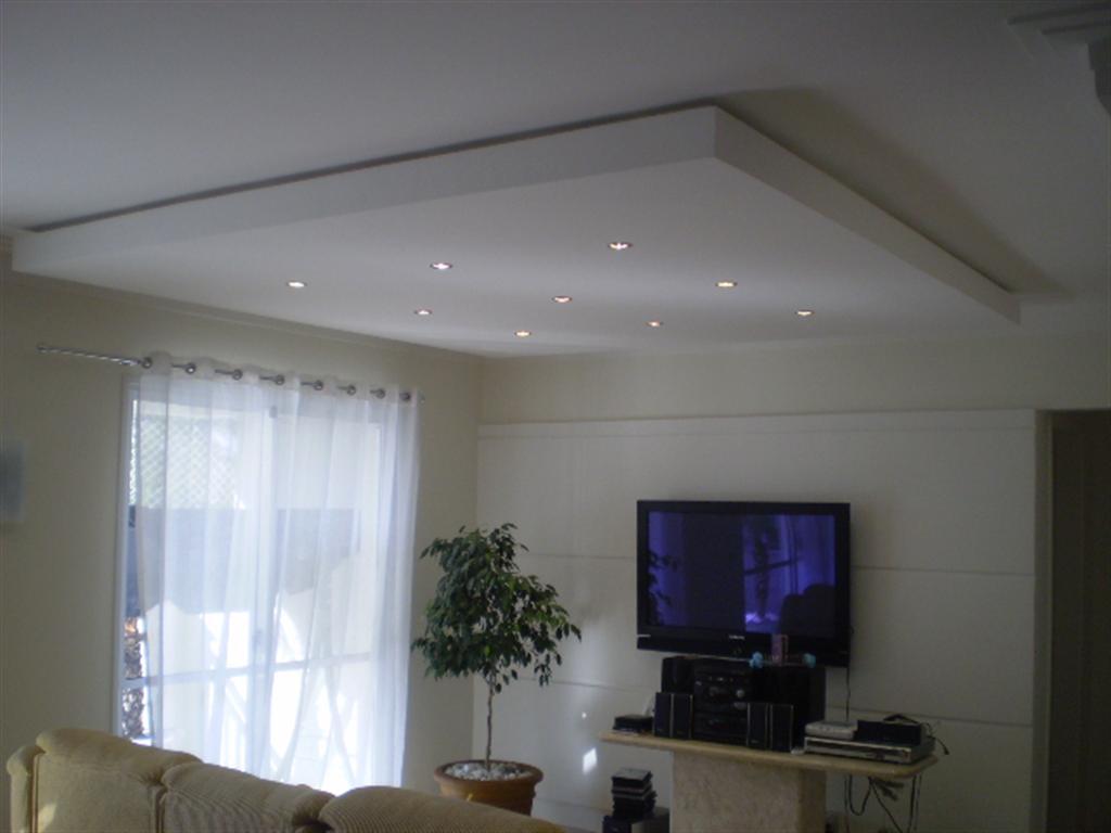 Sala de tv com sanca de gesso rebaixada e iluminação embutida.