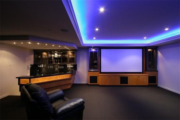 Sala de tv com bar com iluminação azul embutida na sanca de gesso.