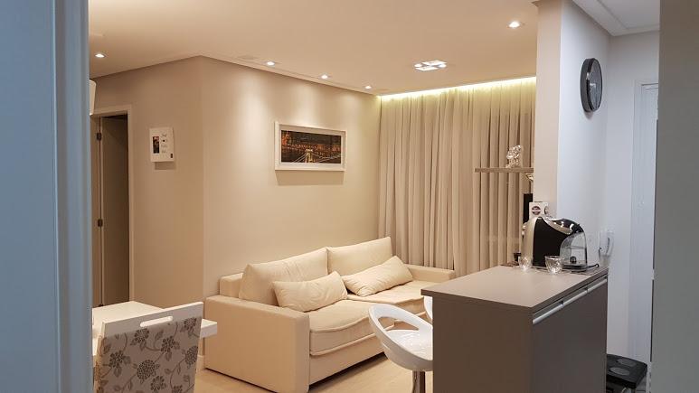 Sala pequena com pequenos pontos de luz na sanca de gesso.
