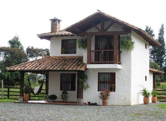 Casa de campo branca com pedrinhas ao redor.