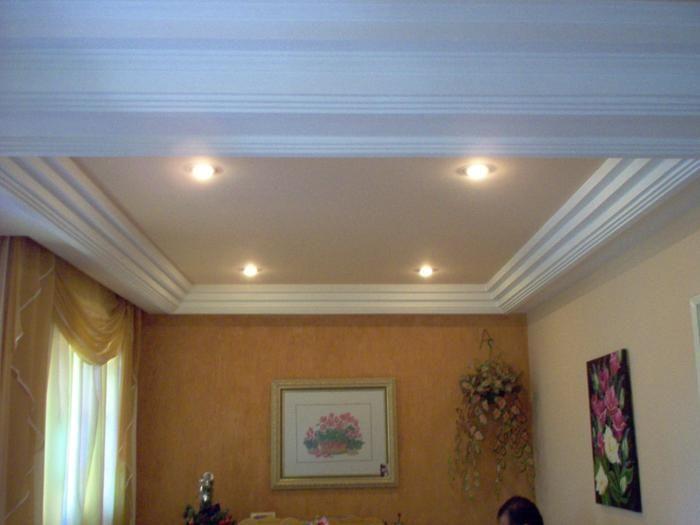 Teto com bordas grossas e quadros nas paredes.
