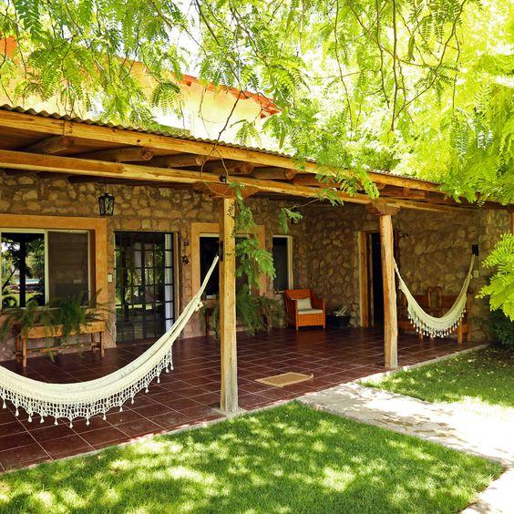 Casa de pedra com redes na varanda.