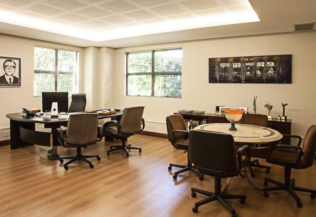 Escritório com duas mesas e quadros na parede.