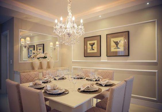 Sala de jantar decorada com quadros e lustre.