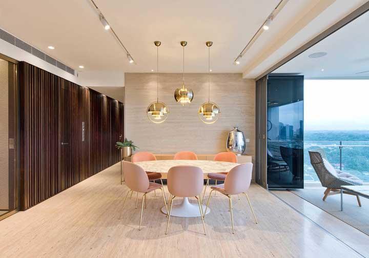 Sala minimalista com três luminárias suspensas sob a mesa.