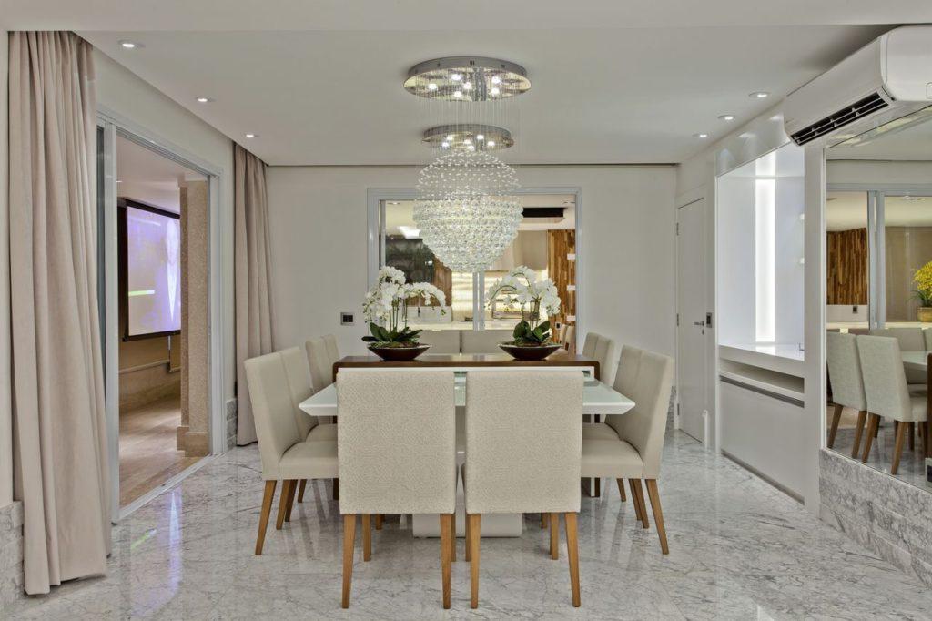 Sala de jantar com ar condicionado, espelho e lustres.