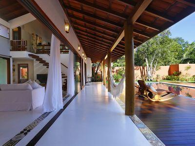 Casa de campo branca com rede na varanda.