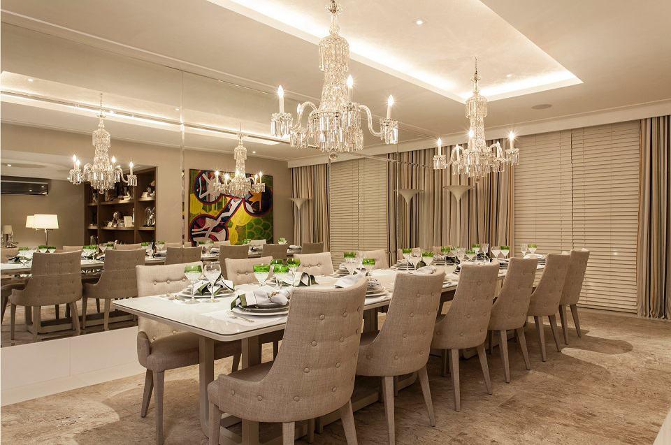 Sala de jantar nude com lustres e iluminação embutida no teto.