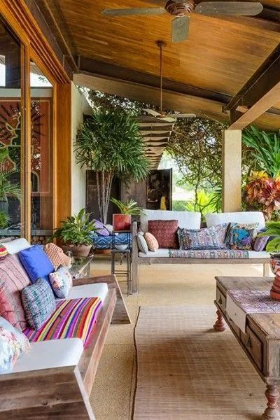 Varanda de casa de campo com sofás rústicos.