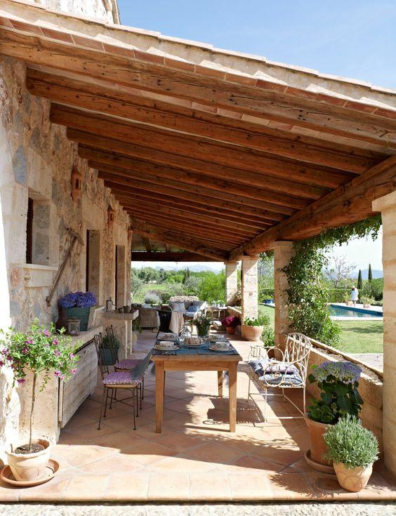 Casa rústica com mesa de jantar na varanda.