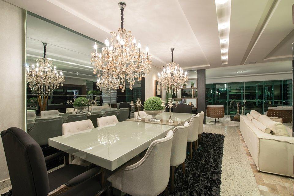 Sala de jantar integrada com a de estar com lustres.