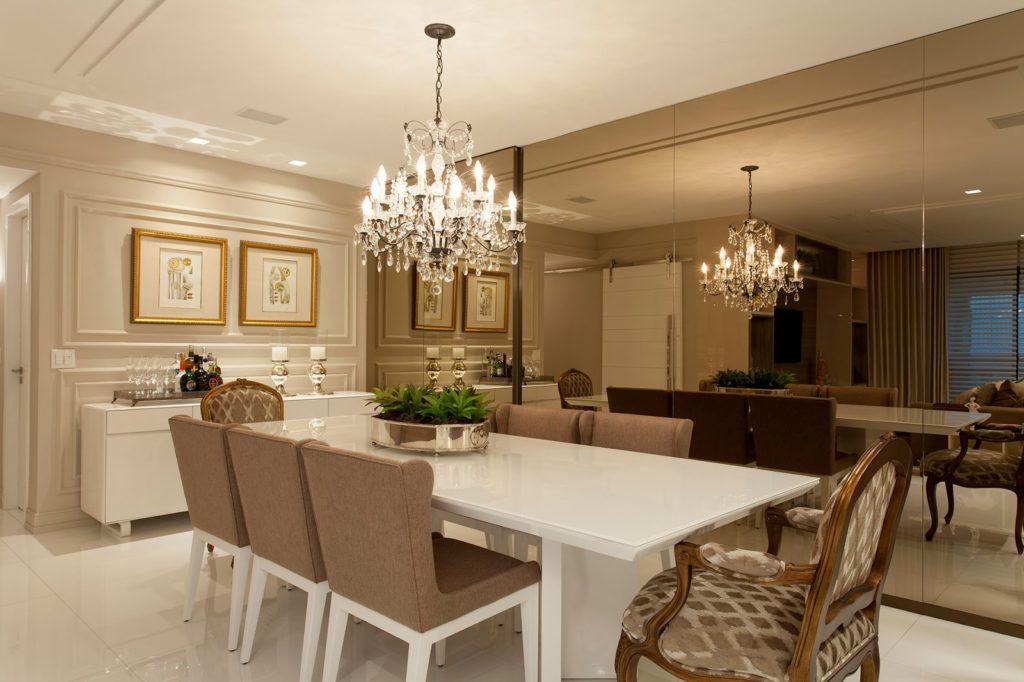 Sala de jantar com parede espelhada e lustre.