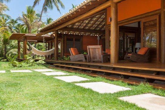 Casa de campo laranja com varanda.