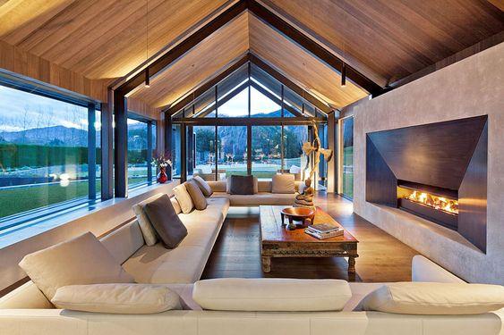 Sala de estar moderna com lareira e paredes de vidro.