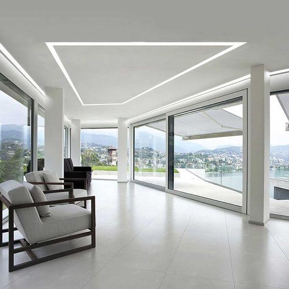 Sala branca toda de vidro com iluminação embutida.