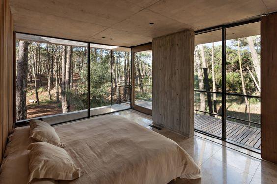 Quarto com varanda e paredes de vidro.