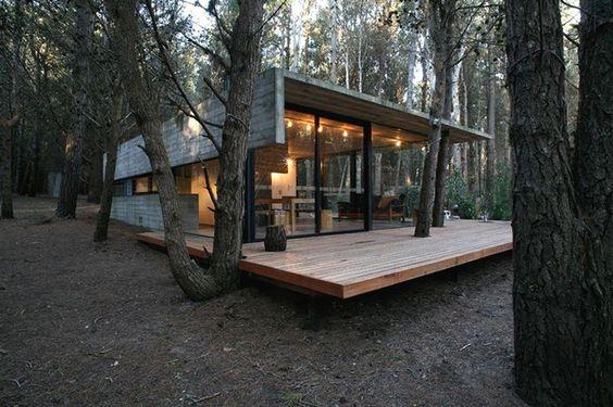 Casa de campo de vidro no meio da floresta.
