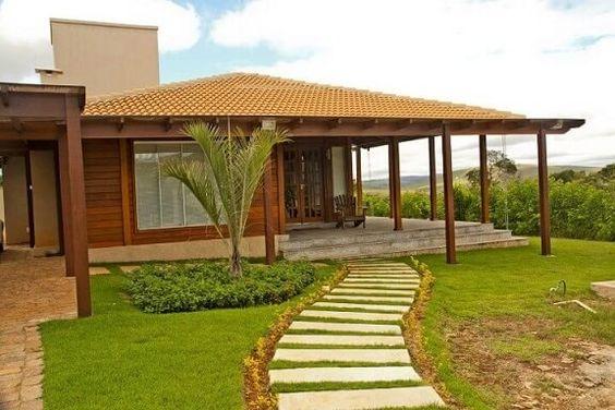 Casa de campo de madeira com caminho de pedra na entrada.