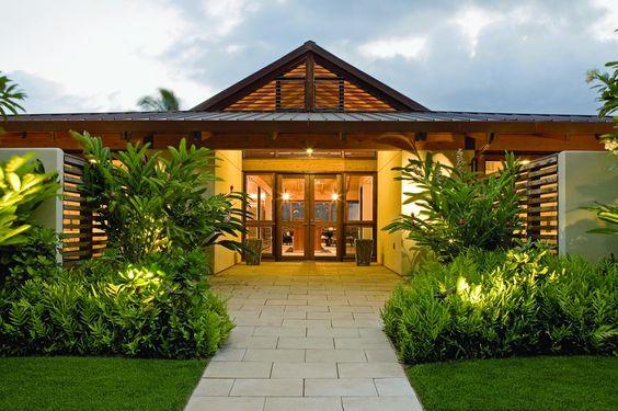 Casa de campo com gramado e jardim na fachada.