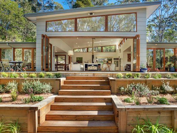 Casa branca com muito vidro e escadaria.
